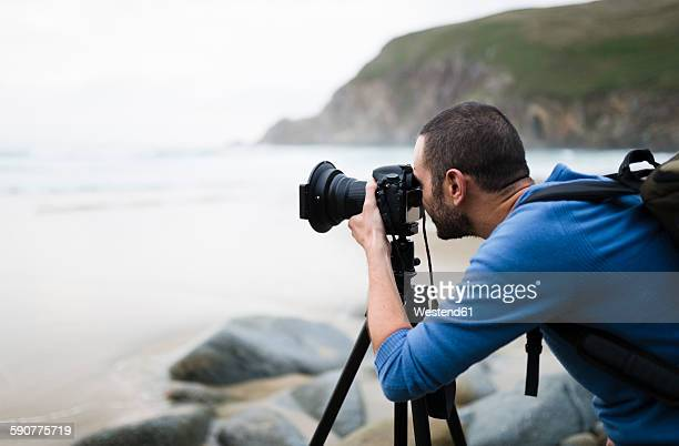 Spain, Valdovino, photographer on the beach with tripod and camera