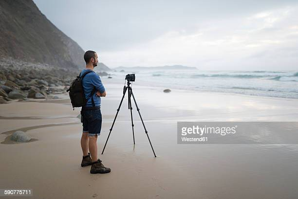 spain, valdovino, photographer standing on the beach taking photos with a tripod - 三脚 ストックフォトと画像
