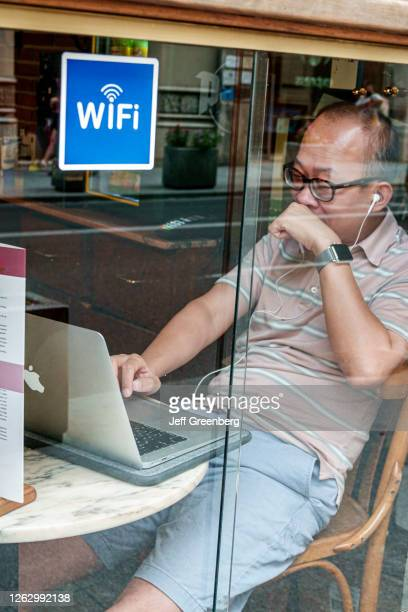 Spain, Valencia, Calle de la Paz, cafe promoting Wi-Fi, man on laptop.