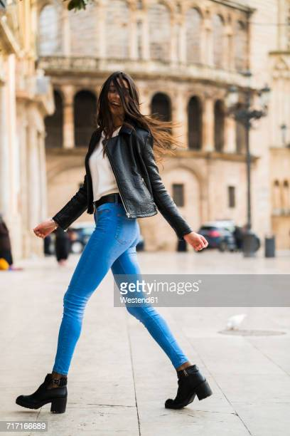 spain, valencia, carefree young woman walking in the city - デニム ストックフォトと画像