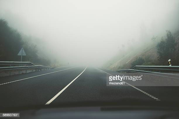 Spain, view from car to empty road at fog