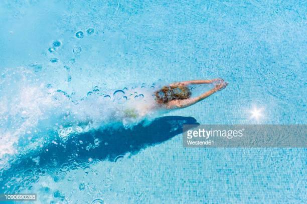 spain, woman diving in swimming pool - schwimmen stock-fotos und bilder