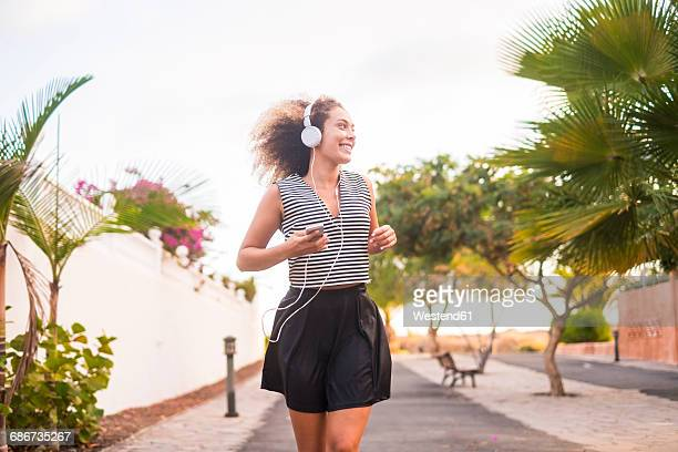 Spain, young woman jogging with smartphone and headphones