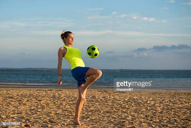 spain, young woman playing soccer at the beach - chutar imagens e fotografias de stock