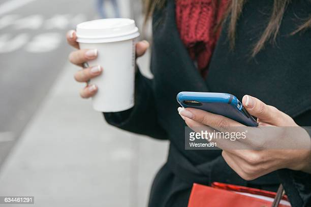 Spain, young woman with smartphone and coffee to go, close-up