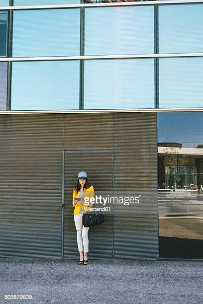 Spain,Catalunya, Barcelona, young modern woman with yellow jacket and tablet computer