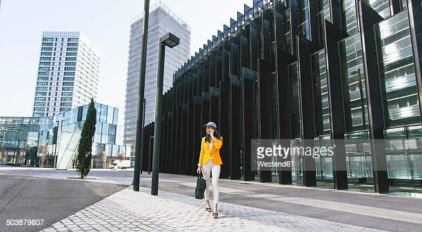 spain,catalunya, barcelona, young modern woman with yellow jacket on the move - courtyard stock pictures, royalty-free photos & images