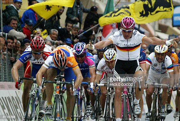 Spainish Oscar Gomez Freire crosses the finish line and wins the 95th edition of MilanSan Remo cycling race as Germany's Erik Zabel raises his arms...