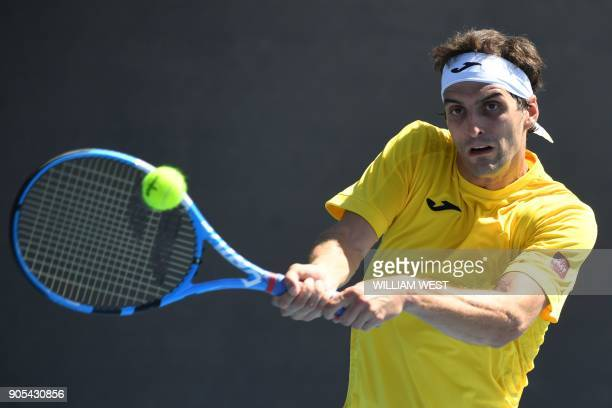 Spain's Albert RamosVinolas hits a return against Jared Donaldson of the US during their men's singles first round match on day two of the Australian...