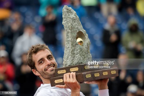 Spain's Albert Ramos-Vinolas raises his trophy after winning against Germany's Cedrik-Marcel Stebe during their men's single final match at the Swiss...