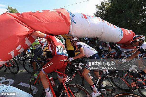 Spain's Alberto Contador Belgium's Jurgen Van den Broeck and Netherlands' Stef Clement try to pass under the deflated arch of the last kilometer of...