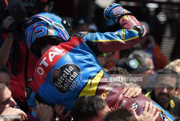 Spain's Alex Marquez celebrates with his team after winning the Italian Moto2 category Grand Prix at the Mugello race track on June 2 2019 in...