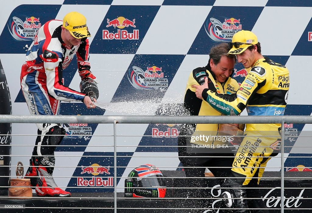 Spain's Alex Rins (R) is sprayed with champagne by Great Britain's Sam Lowes (L) after Rins won the the 2016 Grand Prix of the Americas Moto2 race at circuit of the Americas, in Austin, Texas on April 10, 2016. Lowes came in second in the race. / AFP / Thomas B. Shea