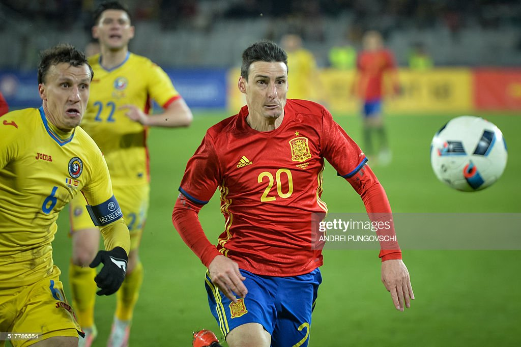Spains Aritz Aduriz and Romanias Vlad Iulian Chiriches ie for the ball during the friendly football match between Romania and Spain in Cluj Napoca, Romania on March 27, 2016. / AFP / ANDREI
