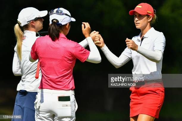 Spain's Azahara Munoz greets Britain's Jodi Shadoff and Taiwan's Hsu Wei-ling after round 1 of the womens golf individual stroke play during the...