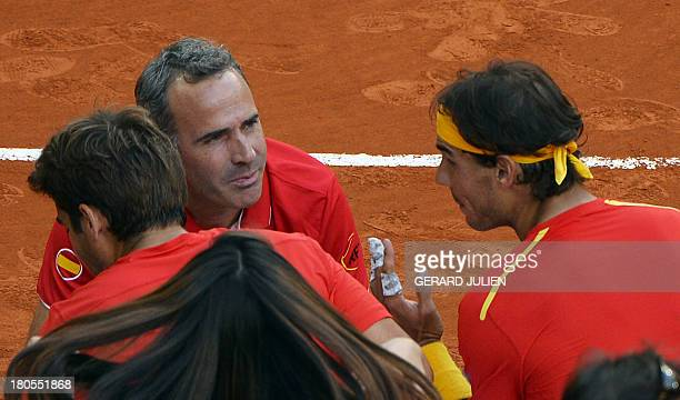 Spain's captain Alex Corretja congratulates Spanish player Rafael Nadal and Marc Lopez at the end of their doubles against against Ukraine's Denys...