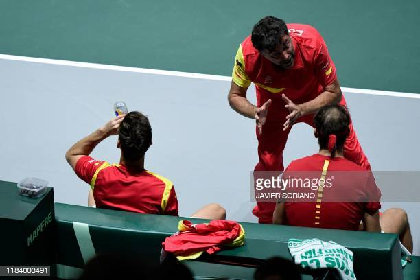 Spain's captain Sergi Bruguera talks to Spain's Rafael Nadal and Spain's Marcel Granollers during the doubles quarter-final tennis match against...