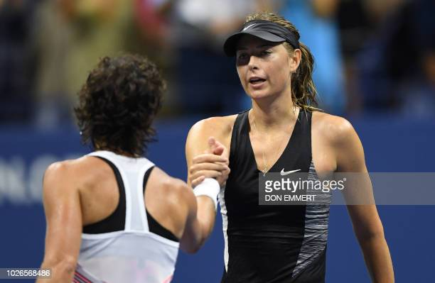 Spain's Carla Suarez Navarro shakes hands with Russia's Maria Sharapova at the net after winning during their 2018 US Open Women's Singles tennis...