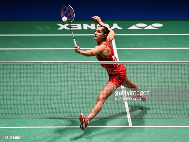 TOPSHOT Spain's Carolina Marin hits a return against Japan's Nozomi Okuhara during the women's singles final at the Japan Open Badminton...
