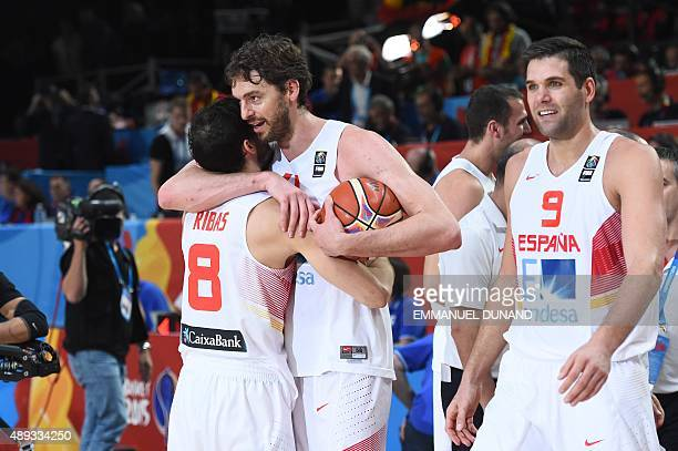 Spain's center Pau Gasol embraces Spain's point guard Pau Ribas as Spain's power forward Felipe Reyes looks on as they celebrate after Spain won the...
