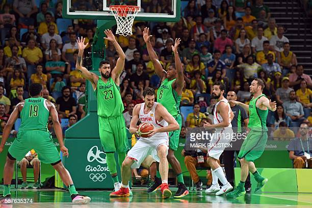 Spain's centre Pau Gasol holds on to the ball next to Brazil's shooting guard Leandro Barbosa Brazil's centre Augusto Lima and Brazil's centre...