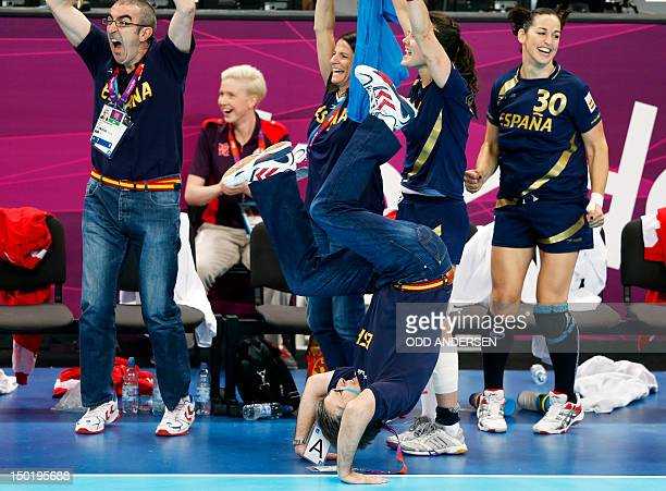 Spain's coach Jorge Duenas de Galarza makes a somersault at the final whistle in the women's bronze medal handball match South Korea vs Spain during...