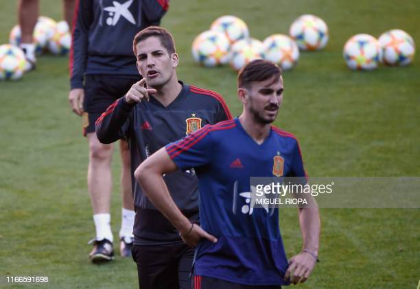Spain's coach Robert Moreno gives instructions behind Spain's midfielder Fabian Ruiz attend a training session at El Molinon stadium in Gijon on...
