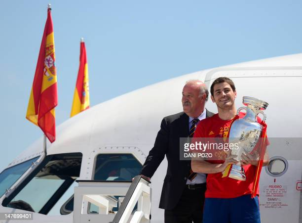 Spain's coach Vicente del Bosque stands as Spain's captain and goalkeeper Iker Casillas holds the EURO 2012 trophy upon the team's arrival at Barajas...