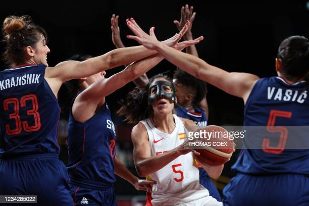 Spain's Cristina Ouvina runs with the ball past Serbia's Tina Krajisnik and Sonja Vasic in the women's preliminary round group A basketball match...