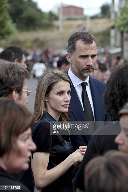 Spain's Crown Prince Felipe and Princess Letizia listen to residents of Angrois near Santiago de Compostela on July 26 2013 A train hurtled off the...