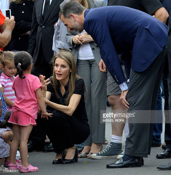 Spain's Crown Prince Felipe and Princess Letizia talk to children in Angrois near Santiago de Compostela on July 26 2013 A train hurtled off the...