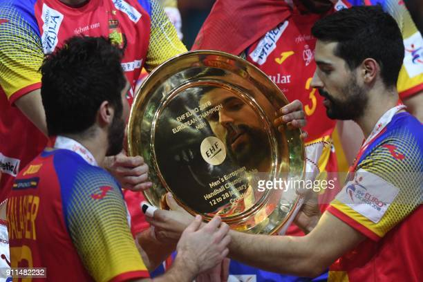 Spain's David Balaguer looks at the EHF European Handball Championship trophy as Spain's players celebrate during the podium ceremony after winning...