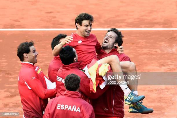 Spain's David Ferrer is carried by teammates as they celebrate after beating Germany during the Davis Cup quarterfinal tennis match at the bullring...