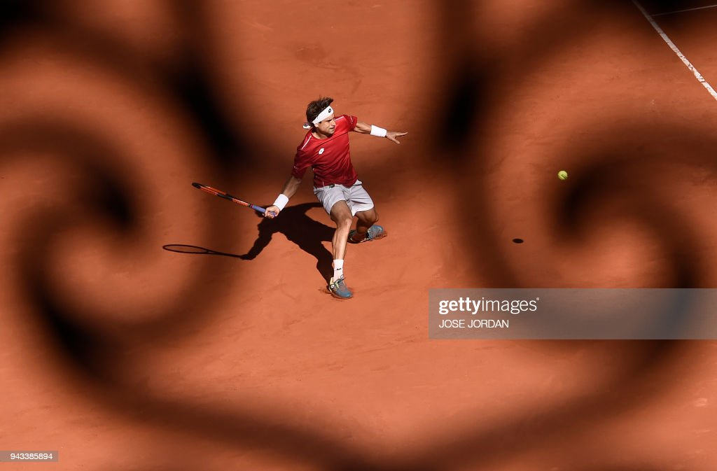 TOPSHOT - Spain's David Ferrer returns the ball during the Davis Cup quarter-final tennis match against Germany's Philipp Kohlschreiber at the bullring of Valencia, on April 8, 2018. /