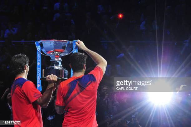 Spain's David Marrero and his partner Spain's Fernando Verdasco pose with the winners' trophy as photographers take pictures during the presentation...