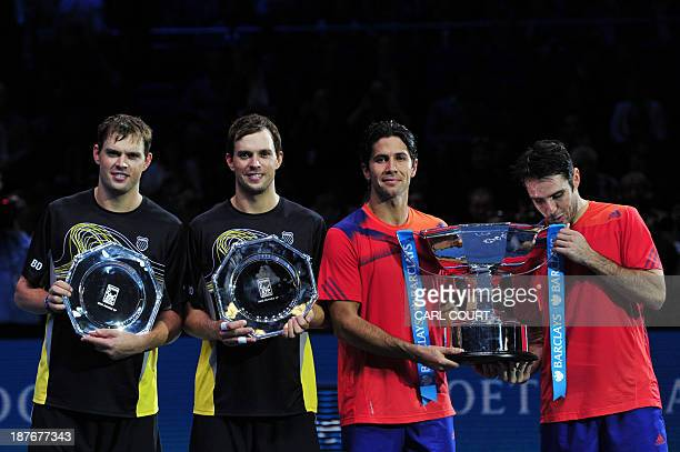 Spain's David Marrero and his partner Spain's Fernando Verdasco pose with the winners' trophy and US player Bob Bryan and US player Mike Bryan pose...