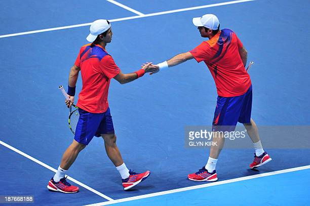 Spain's David Marrero and his partner Spain's Fernando Verdasco touch hands between pointws against US player Bob Bryan and his partner US player...