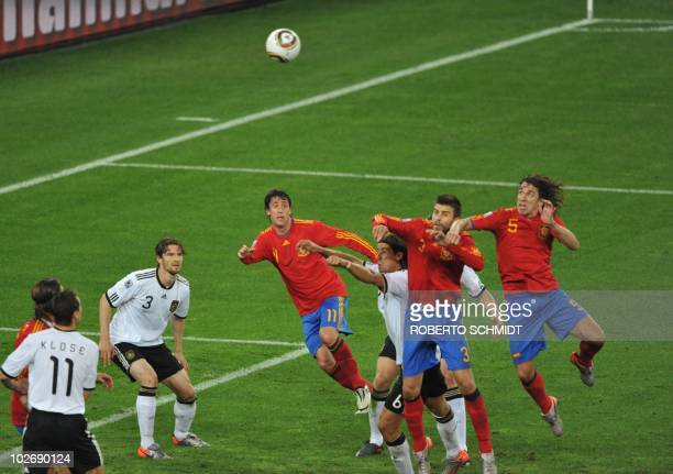Spain's defender Carles Puyol eyes the ball as he jumps up to put home a header for a goal during the 2010 World Cup semifinal football match between...