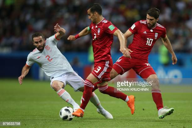 Spain's defender Dani Carvajal competes for the ball with Iran's midfielder Ehsan Haji Safi and forward Karim Ansari Fard during the Russia 2018...