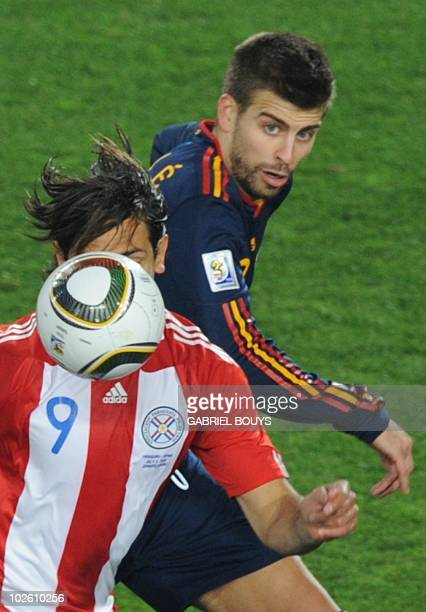 Spain's defender Gerard Pique and Paraguay's striker Roque Santa Cruz vie during their 2010 World Cup quarterfinal football match at Ellis Park...