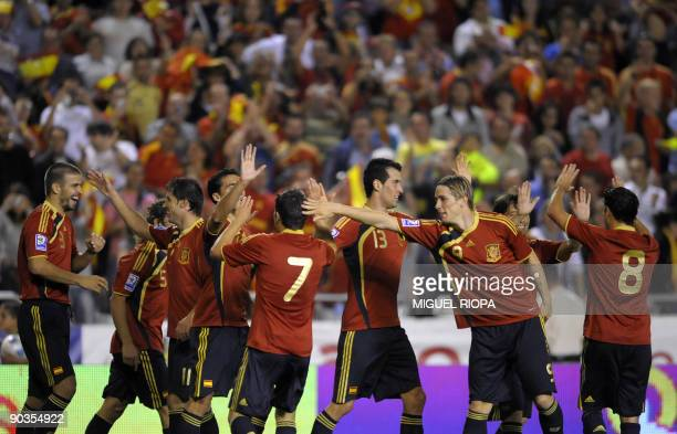 Spain's defender Gerard Pique celebrates with teammates after scoring his team's third goal against Belgium during their World Cup 2010 qualifier...
