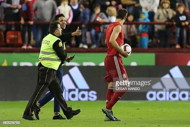 Spain's defender Gerard Pique is given the thumbs up after posing for a selfie with a fan who ran onto the field during the Euro 2016 qualifying...