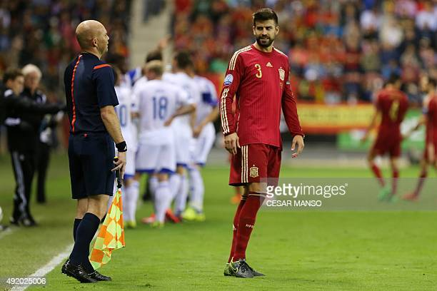 Spain's defender Gerard Pique looks at a line referee during the Euro 2016 qualifying football match Spain vs Luxembourg at Las Gaunas stadium in...