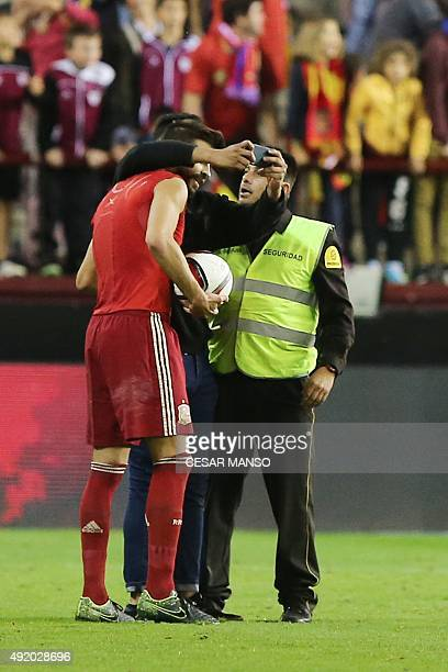 Spain's defender Gerard Pique poses for a selfie with a fan who ran onto the field during the Euro 2016 qualifying football match Spain vs Luxembourg...