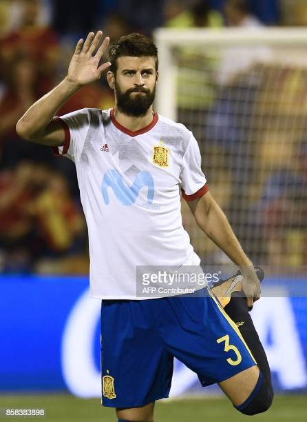 Spain's defender Gerard Pique waves as he warms up before the World Cup 2018 qualifier football match Spain vs Albania at the Jose Rico Perez stadium...