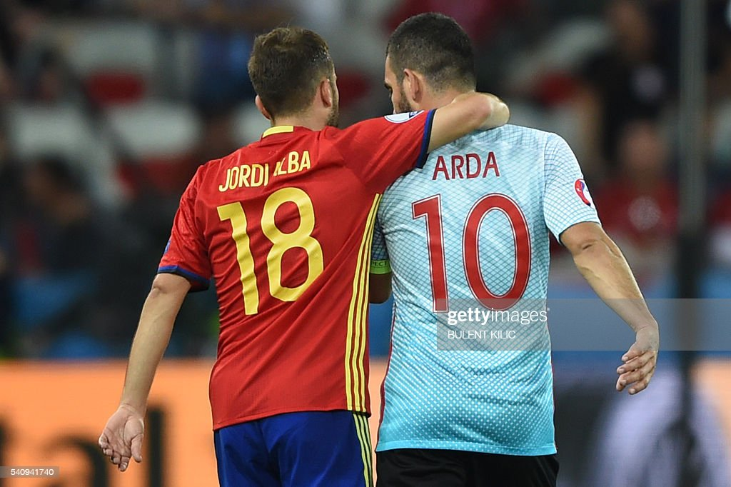 Spain's defender Jordi Alba (L) and Turkey's midfielder Arda Turan share a moment following the Euro 2016 group D football match between Spain and Turkey at the Allianz Riviera stadium in Nice on June 17, 2016. / AFP / BULENT