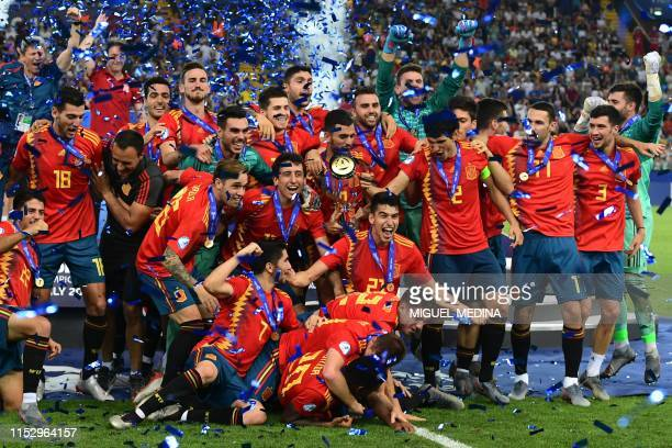 Spain's defender Marc Roca and Spain's players celebrate with the winners' trophy after winning the final match of the UEFA U21 European Football...