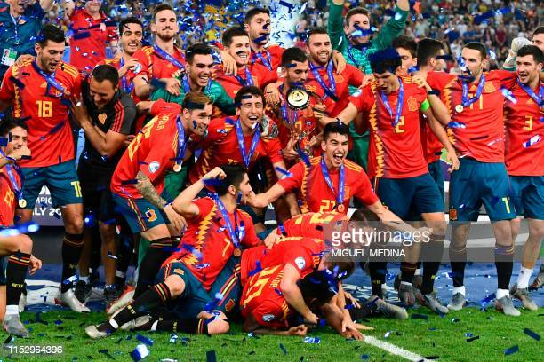 Spain's defender Marc Roca , Spain's midfielder Fabian Ruiz and teammates celebrate with the winners trophy after Spain won the final match of the...