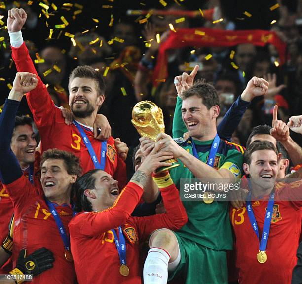 Spain's defender Sergio Ramos and Spain's goalkeeper Iker Casillas raise the trophy as Spain's national football team players celebrate winning the...
