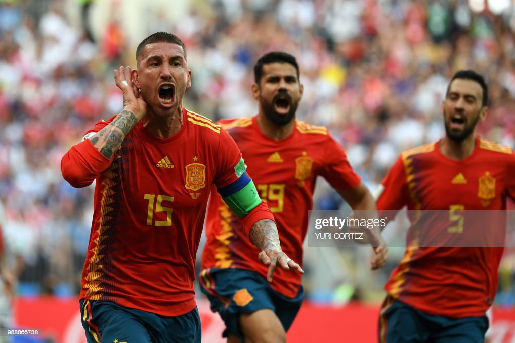 TOPSHOT - Spain's defender Sergio Ramos (L) celebrates pasty Spain's forward Diego Costa (C) and Spain's midfielder Sergio Busquets after an own goal by Russia's defender Sergey Ignashevich during the Russia 2018 World Cup round of 16 football match between Spain and Russia at the Luzhniki Stadium in Moscow on July 1, 2018. (Photo by YURI CORTEZ / AFP) / RESTRICTED